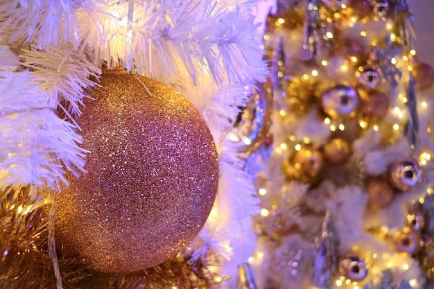 Różowo-złota świecidełka w kształcie bombki z niewyraźną błyszczącą choinką w tle