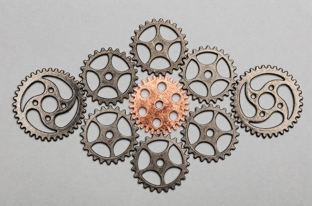 Różowo-złote koło zębate i wiązka srebrnych kół zębatych