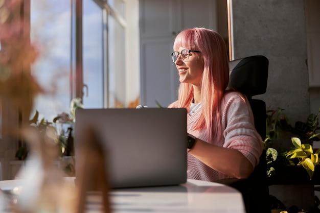 Różowowłosa kobieta w eleganckich okularach działa na laptopie w pobliżu okna w domu