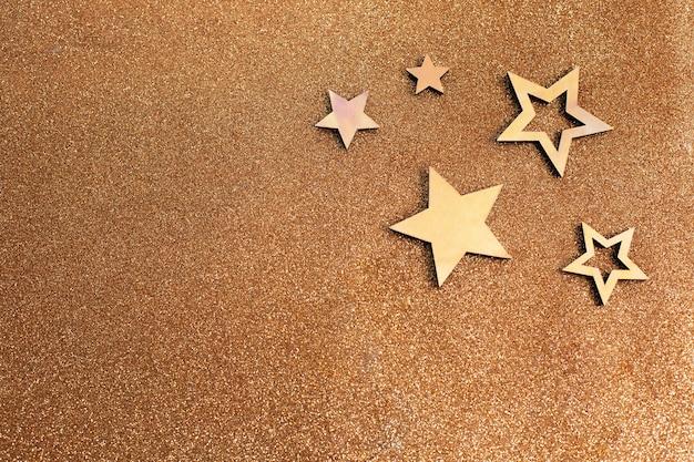 Różowozłote gwiazdki i brokat na jasnobrązowym tle. dekoracja świąteczna. obchody nowego roku.