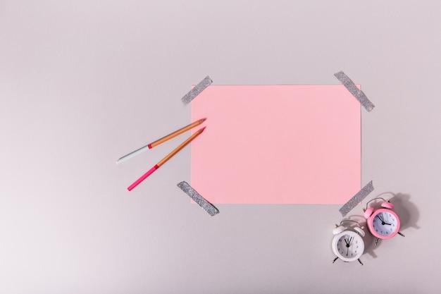 Różowy arkusz a4 przyklejony srebrną taśmą do ściany