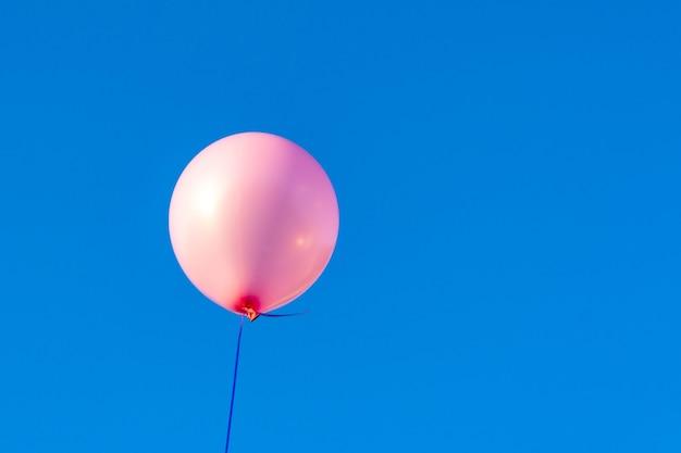 Różowy balon helowy na tle błękitnego nieba