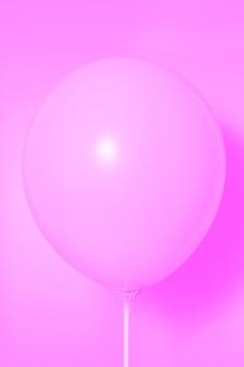 Różowy balon na różowym tle z cieniem. blask boczny.