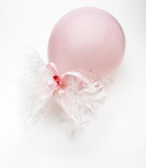 Różowy balon z delikatnymi białymi kokardkami. na białym tle