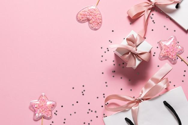 Różowy baner imprezowy z papierową torbą, pudełkiem ze wstążką i błyszczącymi dekoracjami.