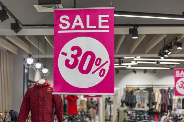 Różowy baner z napisem rabat 30% w sklepie odzieżowym.