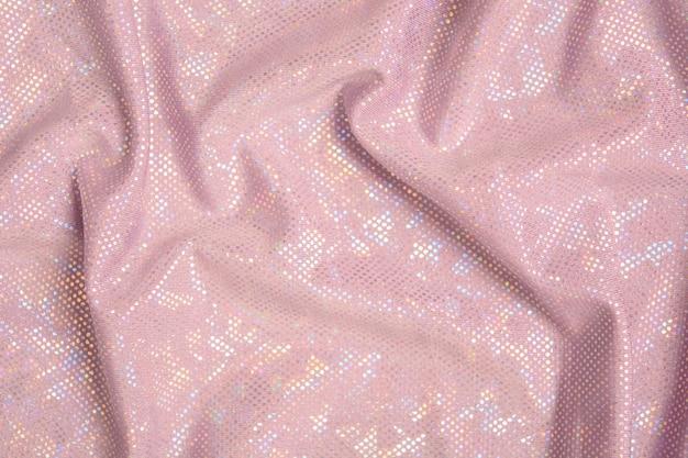 Różowy błyszczący tekstylny tło z łuną. fala teksturowana tkanina. widok z góry