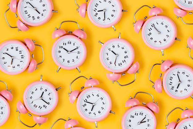 Różowy budzik na żółtym tle.