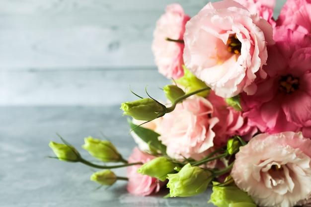 Różowy bukiet kwiatów eustoma na szarym tle