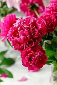 Różowy bukiet kwiatów piwonii na rustykalnym tle z miejsca na kopię