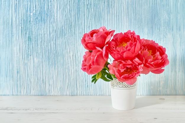 Różowy bukiet piwonii w białym wazonie
