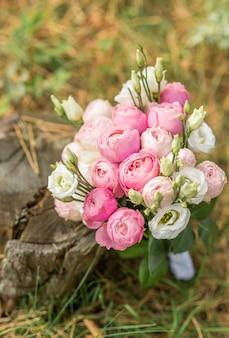 Różowy bukiet ślubny na tle trawy