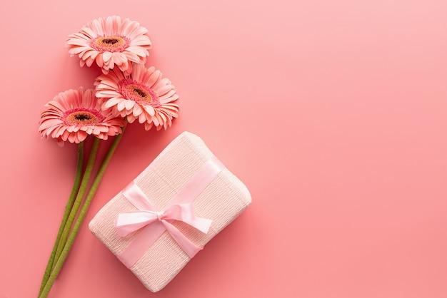 Różowy bukiet stokrotek gerbera i różowy prezent. minimalna konstrukcja płaska. pastelowe kolory