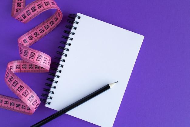 Różowy centymetr i otwarty notatnik na fioletowej powierzchni. widok z góry. koncepcja minimalistycznej diety. miejsce na kopię.