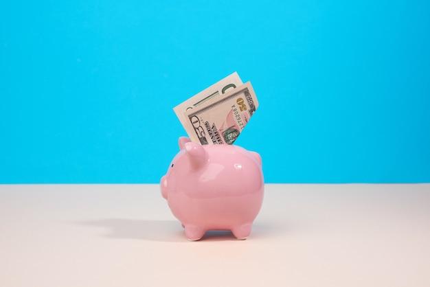 Różowy ceramiczny skarbonka z papierowymi dolarami na niebieskim tle