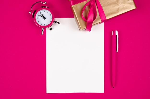 Różowy długopis z papierem na tle bożego narodzenia.