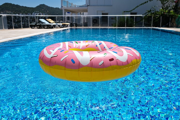 Różowy dmuchany materac pączek w basenie. akcesoria do basenów plażowych. koncepcja wakacji letnich.