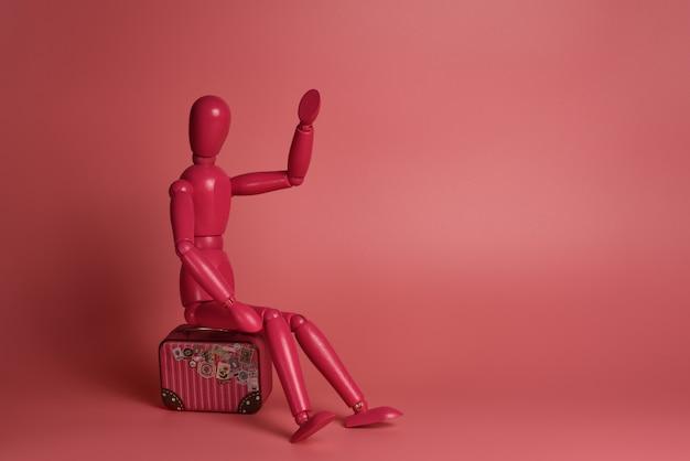 Różowy drewniany mężczyzna siedzi na walizce na różowym tle