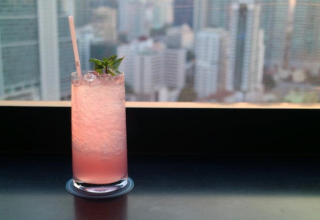 Różowy drink koktajlowy na tarasie na dachu z widokiem na wieżowce w tle