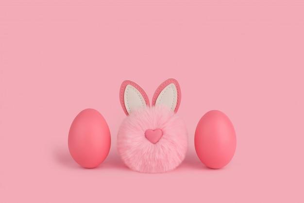 Różowy easter puszysty królik i dwa różowego jajka na różowym tle. śliczny królik pom-pom z nosem w kształcie serca między dwoma pomalowanymi różowymi jajkami. wesołych świąt wielkanocnych. skopiuj miejsce, miejsce na tekst.