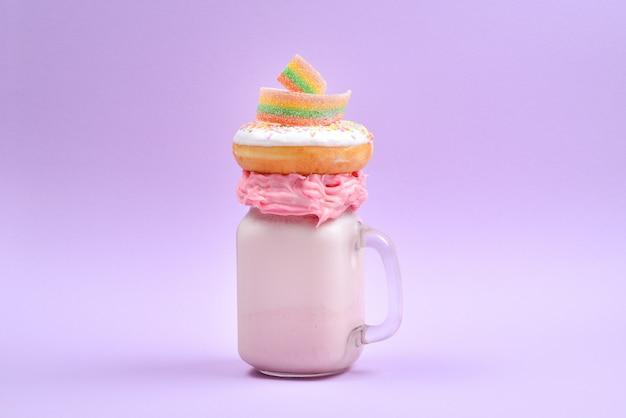 Różowy freakshake z pianką i słodyczami.