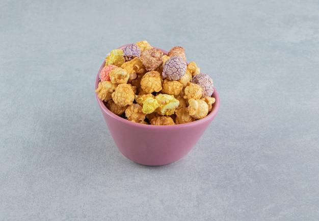 Różowy, głęboki talerz słodkiego, wielobarwnego popcornu.