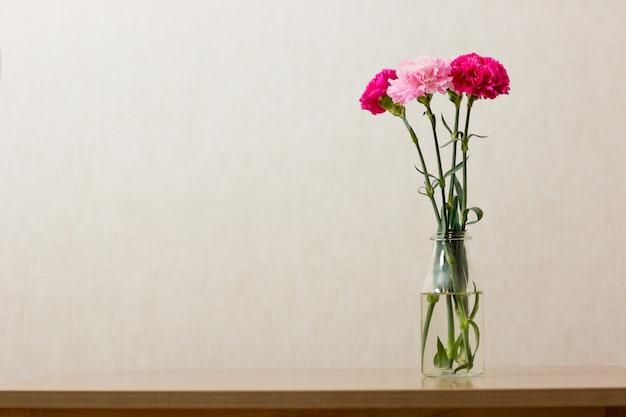 Różowy goździk kwitnie w jasnej butelce na starym drewnie