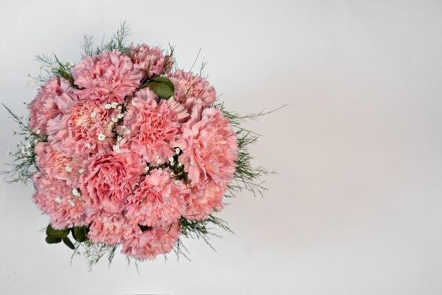 Różowy goździków kwiatów wiadro na białym tle