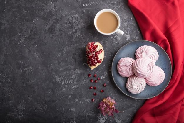 Różowy granatowiec domowej roboty zefir lub marshmallow z filiżanką kawy na czarnym betonowym tle. widok z góry, kopia przestrzeń.
