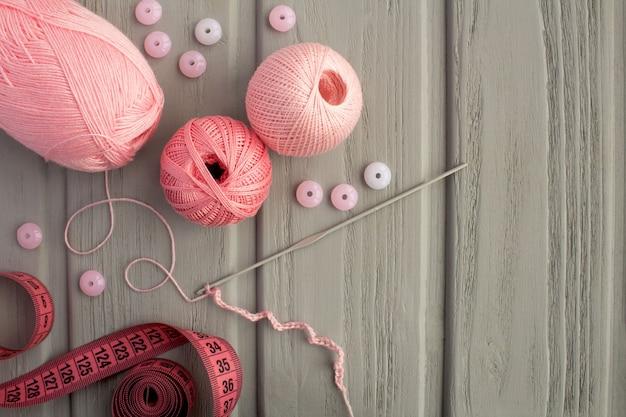 Różowy haczyk na drutach i szydełku na szarym tle drewnianych