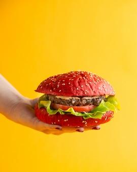 Różowy hamburger kobieta trzymająca burgera z pomidorowym kawałkiem sałaty wołowej i sosem w bułkach burgera