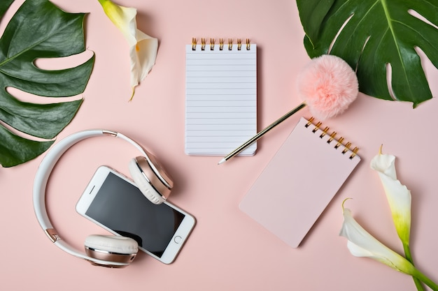 Różowy hełmofon, telefon, pusty notepad i pióro na różowym tle z monstera liściem, odgórny widok