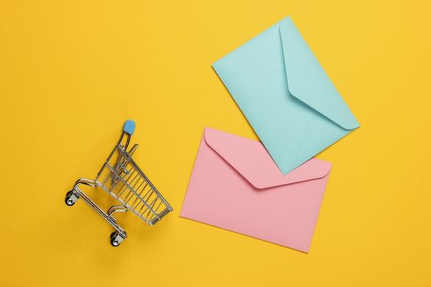 Różowy i niebieski dwie koperty i wózek na zakupy na żółtym tle. makieta na walentynki, wesele lub urodziny