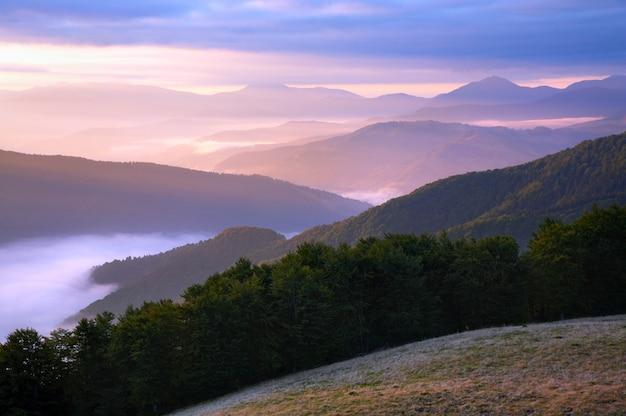 Różowy jesienny poranek górski z promieniem słońca i zamgleniem