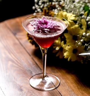 Różowy koktajl przyozdobiony kwiatkiem w szklance martini