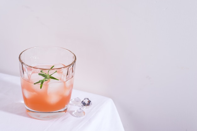 Różowy koktajl z rozmarynem i lodem w szkle na białym obrusie na stole