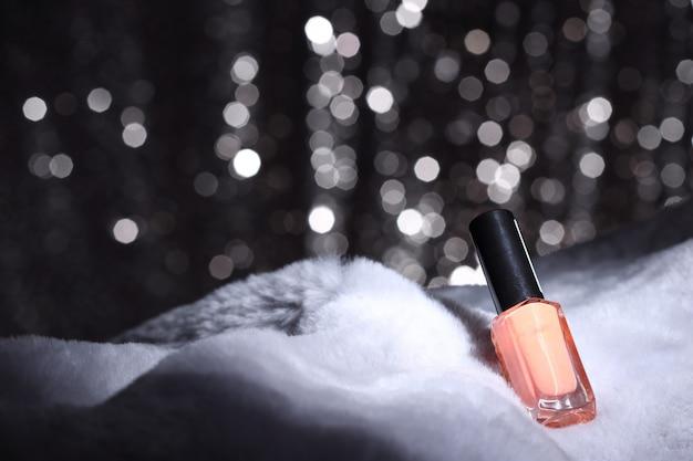Różowy kolor paznokci na futrze i srebrna tapeta