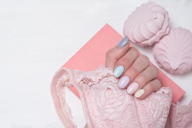 Różowy koronkowy stanik w kobiecej dłoni. delikatny manicure. zbliżenie