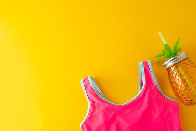 Różowy kostium kąpielowy i słoik ananasa na juiuce. lato tło z kopii przestrzenią.