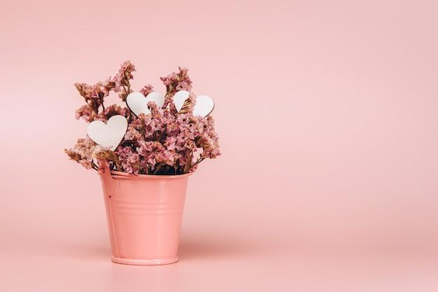 Różowy kosz metalowy z naturalnymi kwiatami i drewnianymi serduszkami na różowym tle.