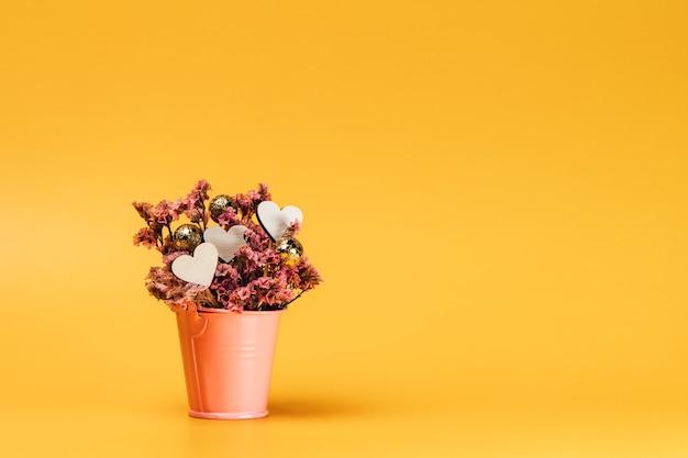 Różowy kosz metalowy z naturalnymi kwiatami i drewnianymi serduszkami.