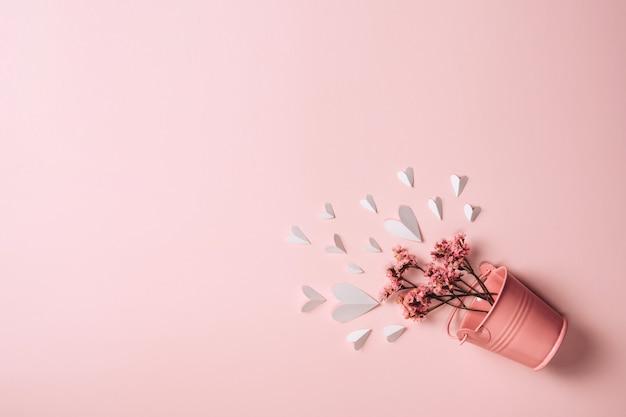 Różowy kosz metalowy z naturalnymi kwiatami i papierowymi serduszkami na różowym tle.