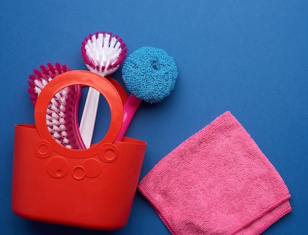 Różowy kosz z gąbkami do prania, pędzle na niebiesko