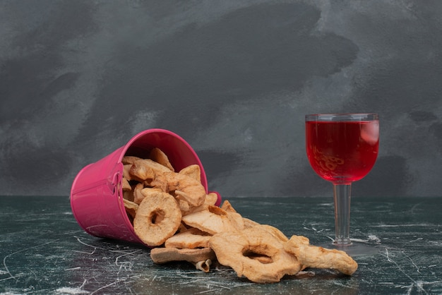 Różowy kosz z suszonymi owocami i szklanką soku na marmurowej ścianie.