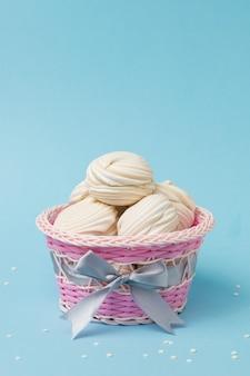 Różowy kosz z szarą wstążką wypełnioną bezą. pyszna słodycz jajek i cukru.