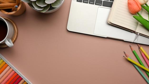 Różowy kreatywny płaski obszar roboczy z papeterią, laptopem, narzędziami do malowania, dekoracjami, miejscem do kopiowania, widokiem z góry