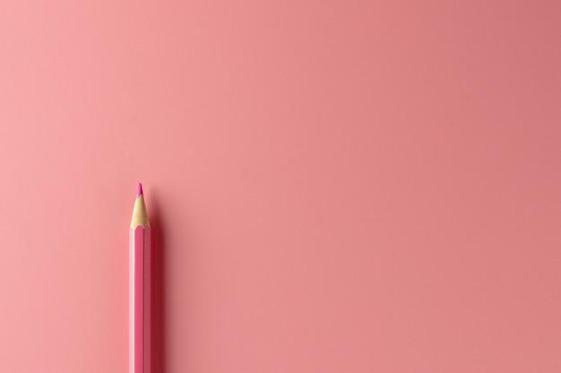 Różowy kredkowy ołówek na menchiach tapetuje tło.