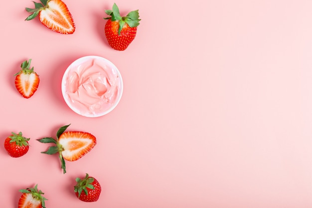 Różowy krem lub maska na twarz, świeże dojrzałe truskawki na różowym tle. pojęcie piękna. pojęcie kosmetyków naturalnych. leżał płasko, kopiuj przestrzeń.