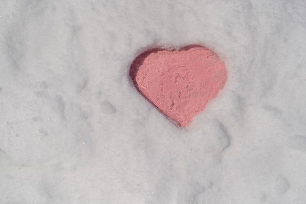 Różowy kształt serca na białym świeżym śniegu w zimie, z bliska. zimowy symbol miłości jako pozdrowienia w kształcie romansu, skopiuj tło przestrzeni
