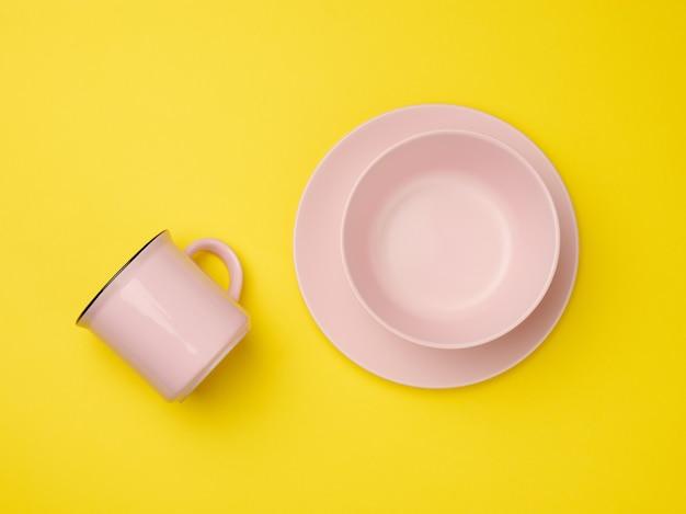 Różowy kubek ceramiczny i pusty talerz ceramiczny na żółtym tle, widok z góry